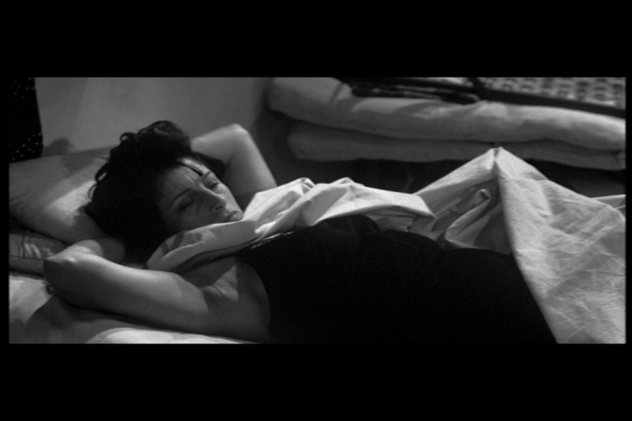 fotogrammi tratti da Nella città l'inferno, presentazione ritardata di Egle che giace sdraiata sulla branda e che si mostra alla camera in una posa vulnerabile e sensuale