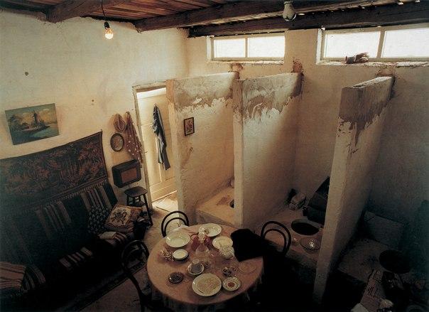 Il'ja e Emilia Kabakov. Tualet (1992). Pietra, cemento, legno, pittura, bagni maschili, bagni femminili, oggetti casalinghi, mobili. Misure approssimative: 4,50x4,17x1,1 m. Installazione per la prima volta presentata a 'Documenta IX', Kassel, Germania