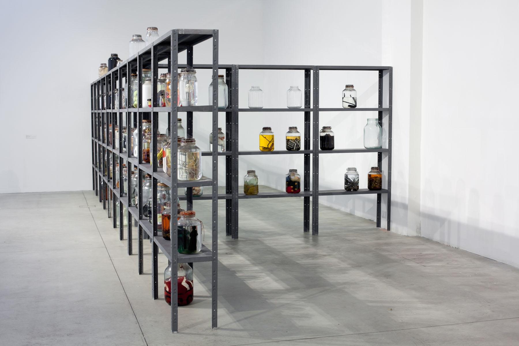 Sergej Volkov, Magazzino d'arte (1990). Scaffali di ferro, barattoli di vetro, oggetti in glicerina, installazione ambiente